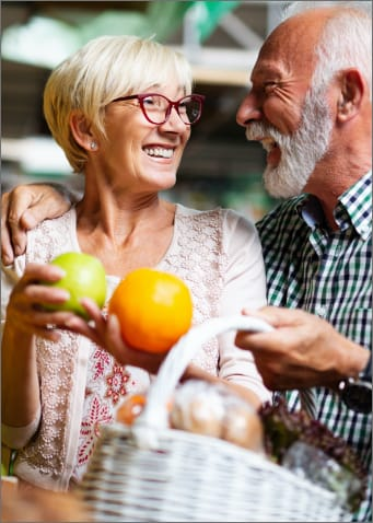 Mature couple buying and orange and an apple at the market.