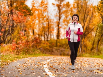 Mataure woman jogging in a foresst of fall leaves.