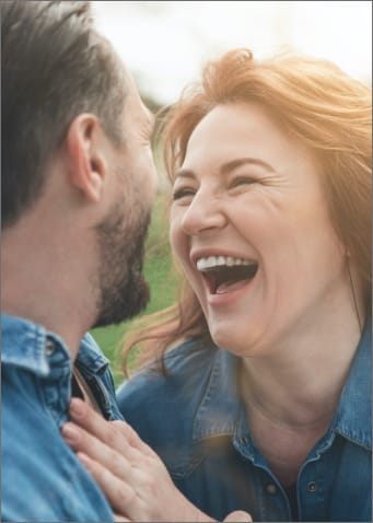 Close up of red headed woman laughing at her husband